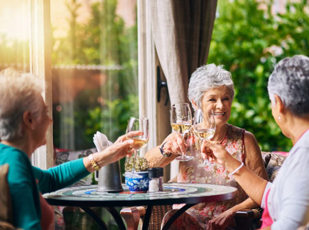seniors clinking their wine glasses together over brunch