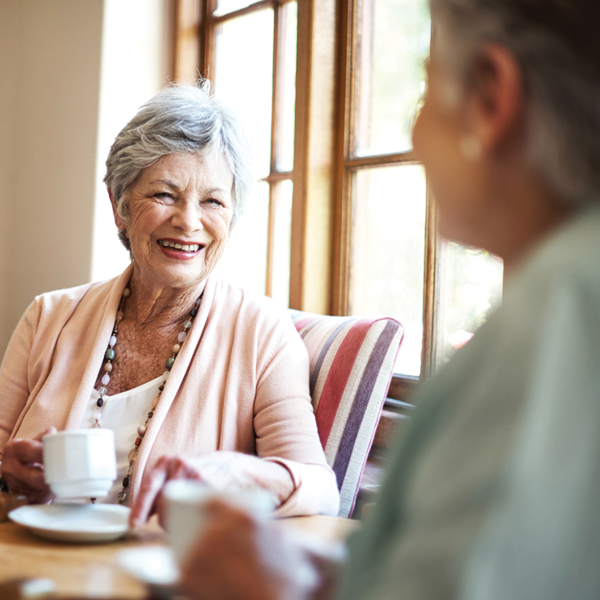 senior women laughing together while enjoying coffee