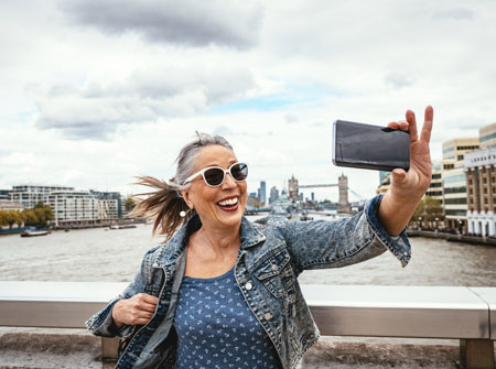 woman smiling and taking a photo of herself near a harbor