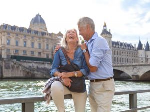 senior couple standing in front of a scenic canal laughing and holding each other