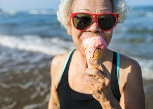 senior woman enjoying a strawberry ice-cream cone on the beach