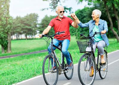 senior couple enjoying a bike ride through a park together