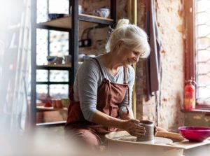 senior woman shaping clay on a pottery wheel