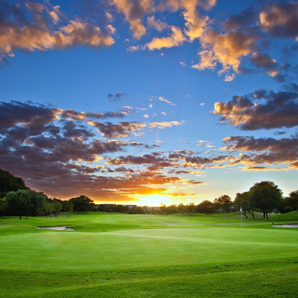 sun setting on a golf course fairway