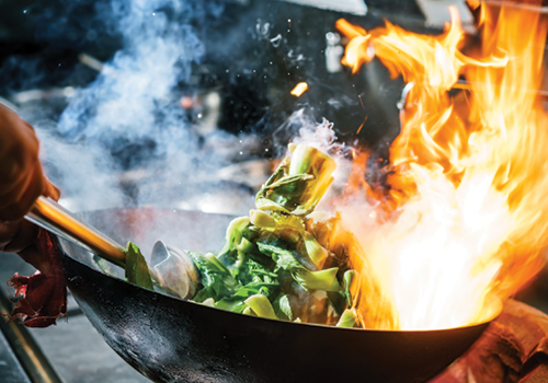 chef flipping vegetables in a wok above an open flame