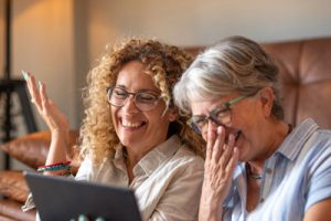 senior and adult daughter laughing and looking at a tablet together